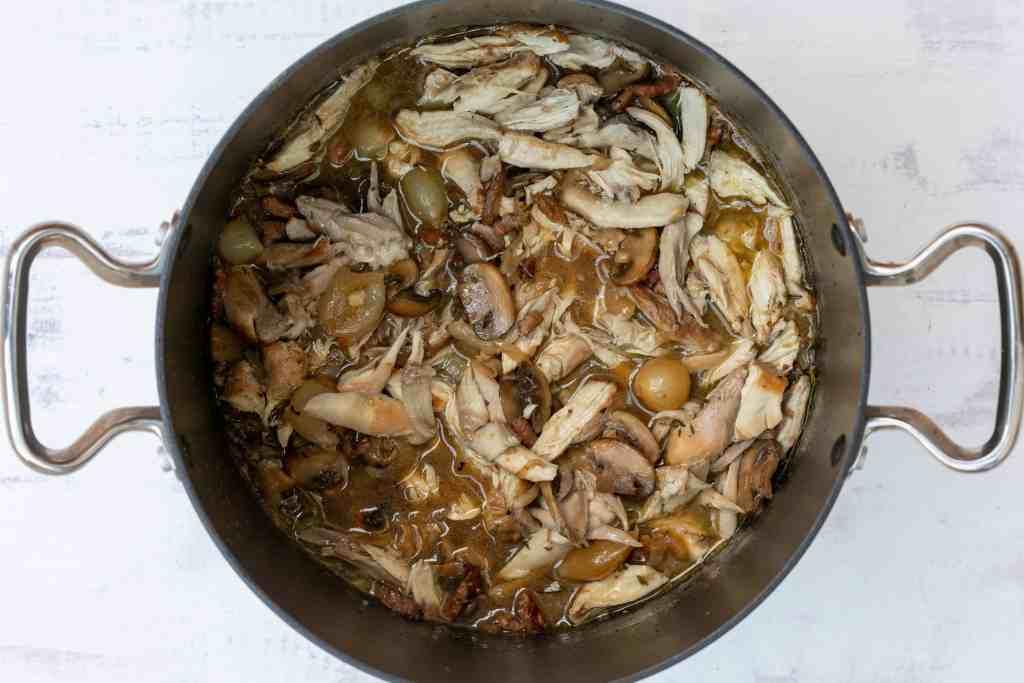 finished coq au vin blanc in large saucepan