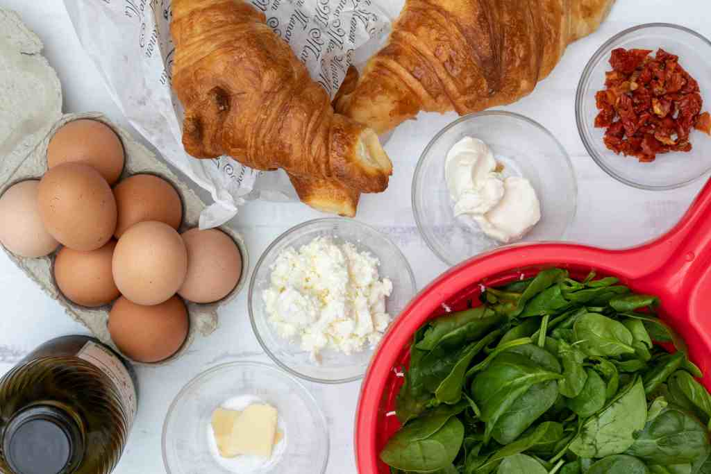 ingredients for croissant breakfast sandwiches: eggs, croissants, sun-dried tomatoes, spinach, cream cheese, butter, and feta