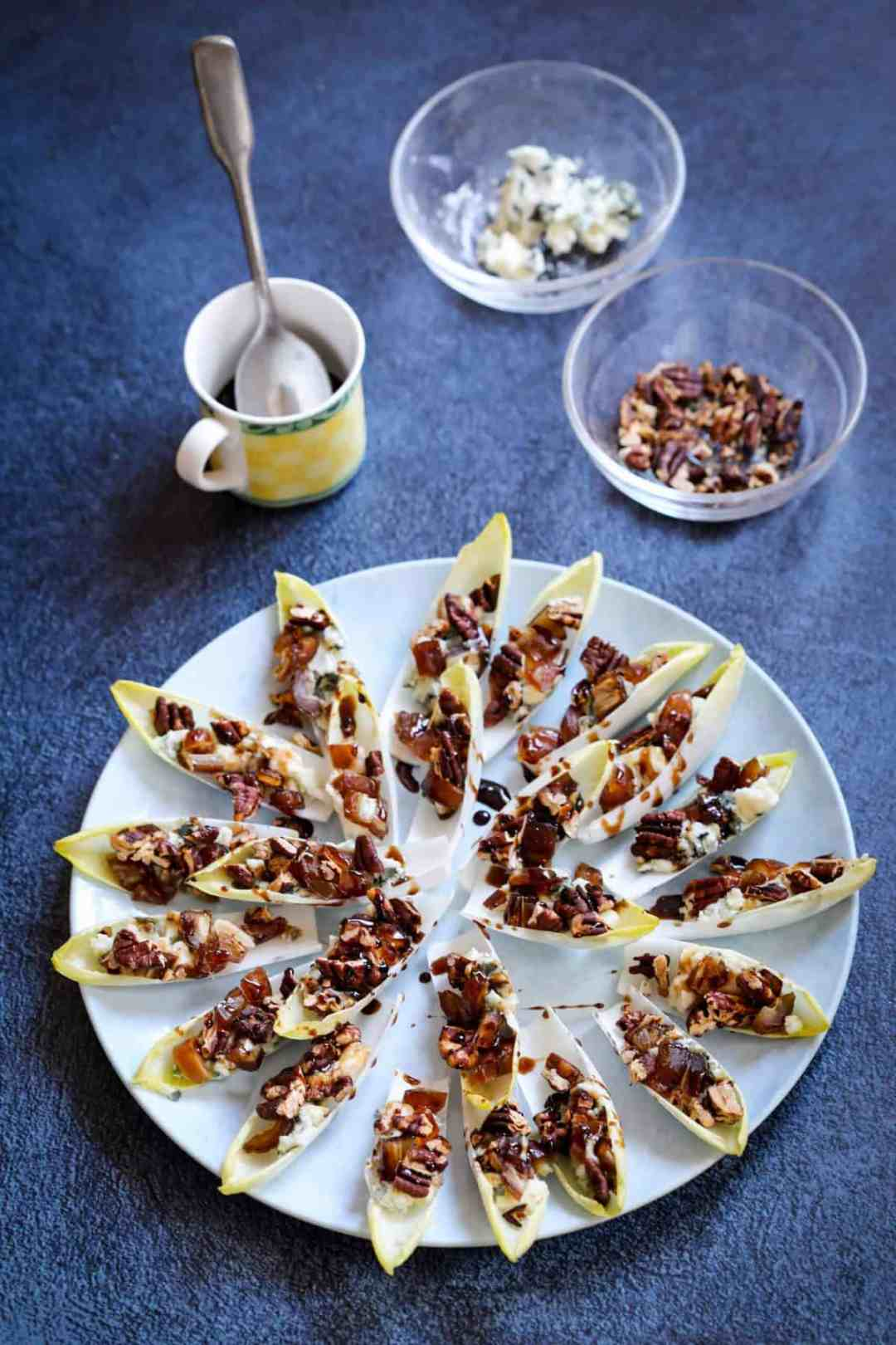 Endive appetizer with blue cheese and pecans with bowls of blue cheese and pecans and balsamic syrup