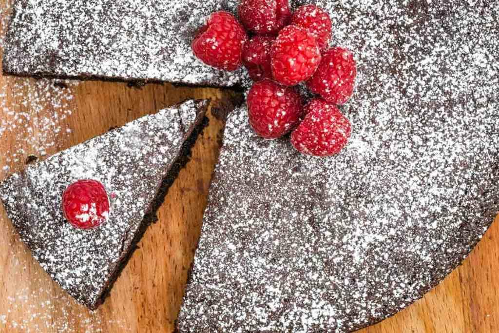 almond flour chocolate cake with powdered sugar and raspberries