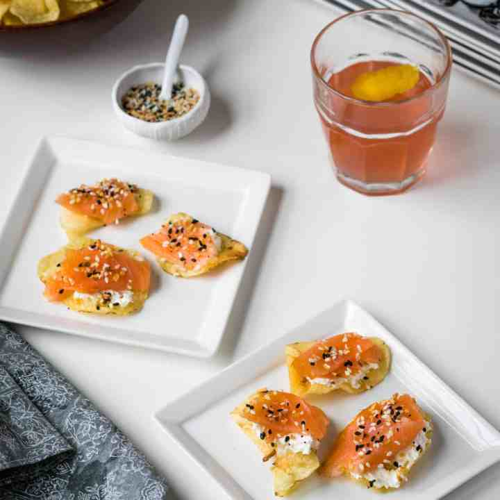 smoked salmon potato chips on plates with cocktail glass and bowl of chips