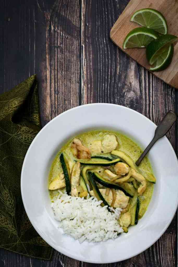 bowl of chicken curry with rice and lime slices