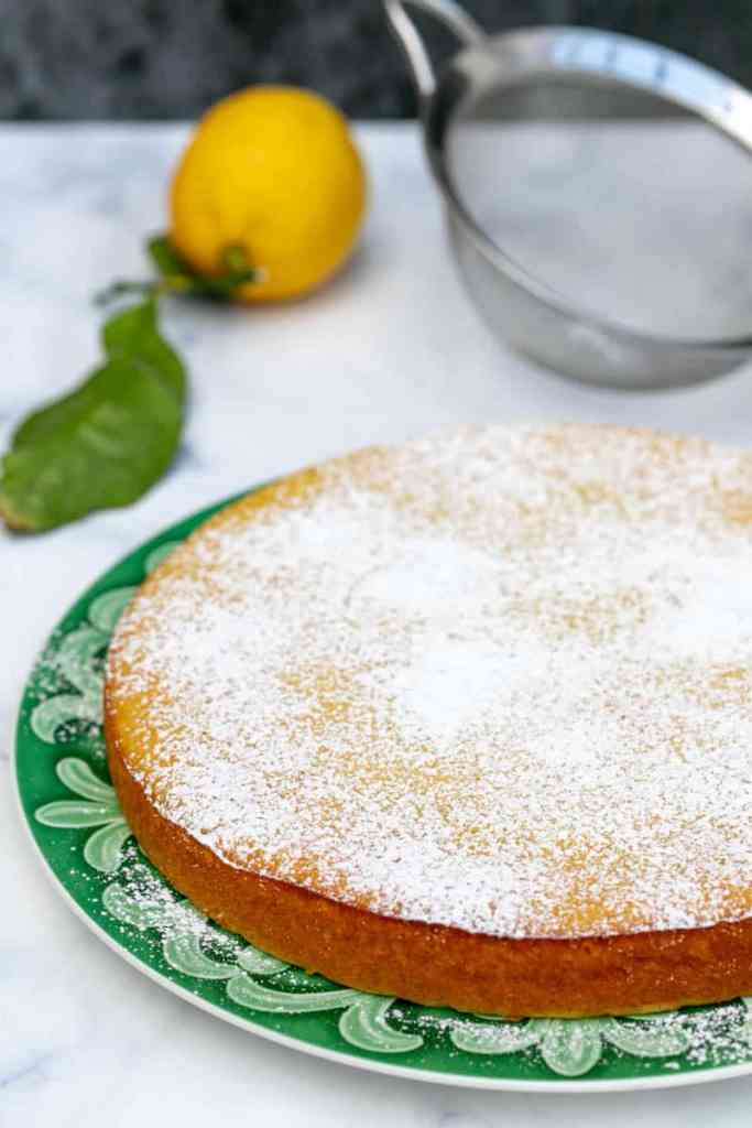 lemon ricotta cake with powdered sugar with lemon and sieve in background