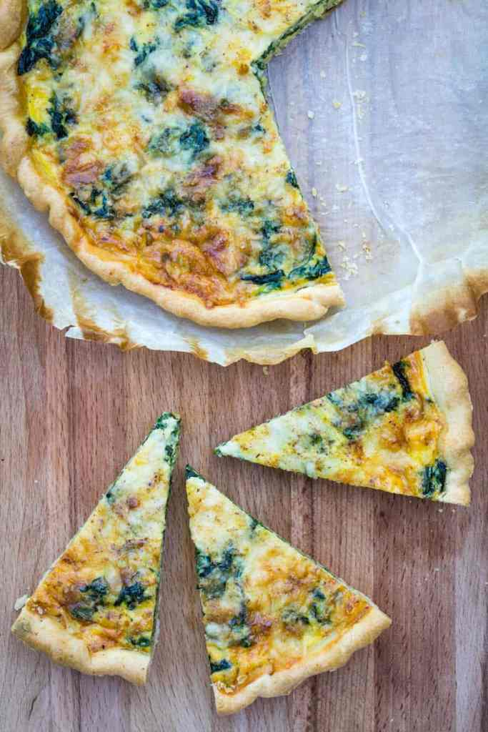 slices of quiche Florentine next to whole quiche with sliced cut out