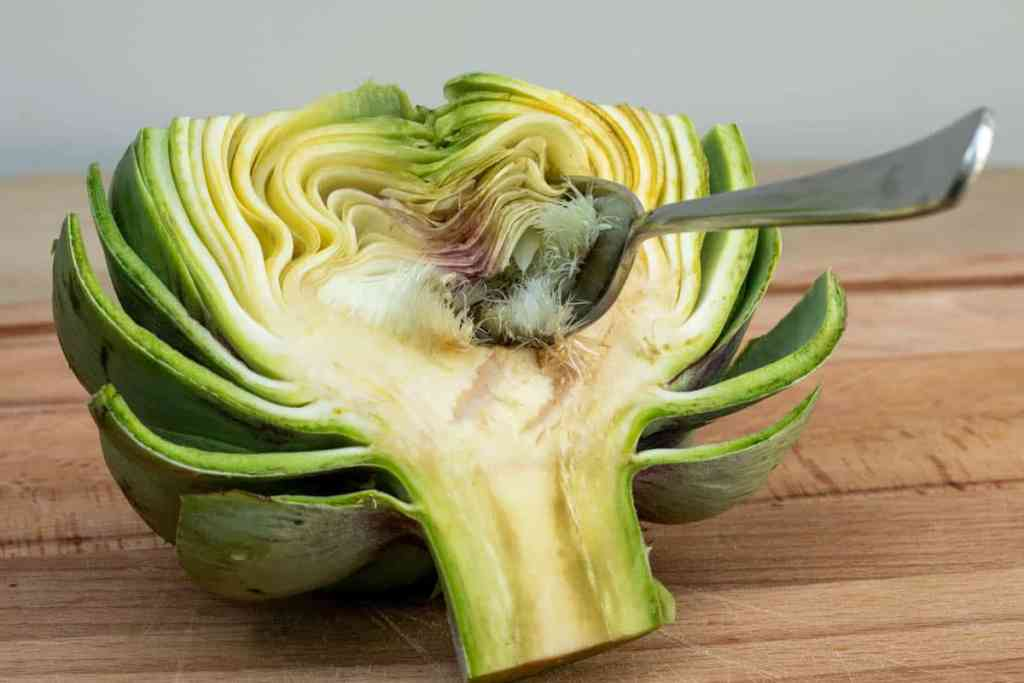 half of an artichoke with spoon showing how to remove the hairy choke in the inside