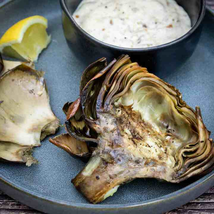 plate with roasted artichoke half with bowl of dipping sauce and lemon wedge
