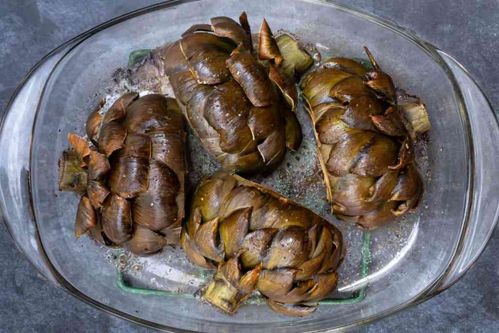 roasted artichoke halves face down in baking dish after roasting
