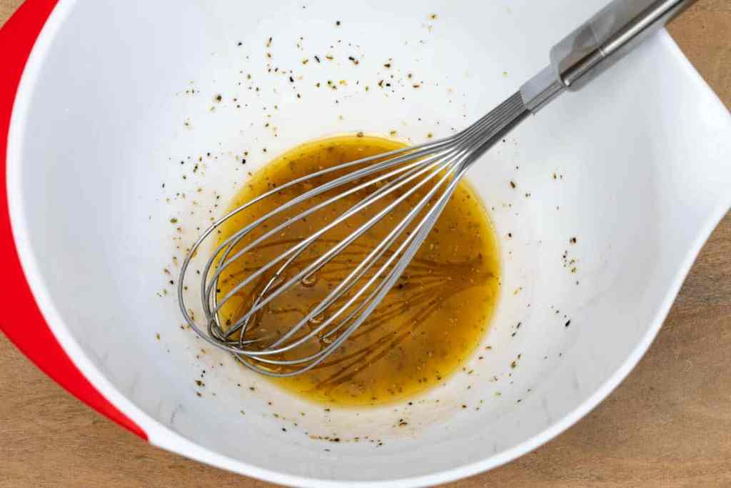 large white bowl with red wine vinaigrette in it and whisk