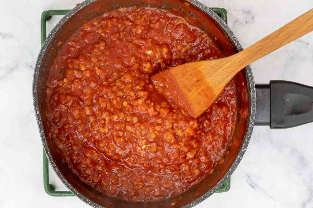 lentil bolognese sauce in large saucepan with wooden spatula