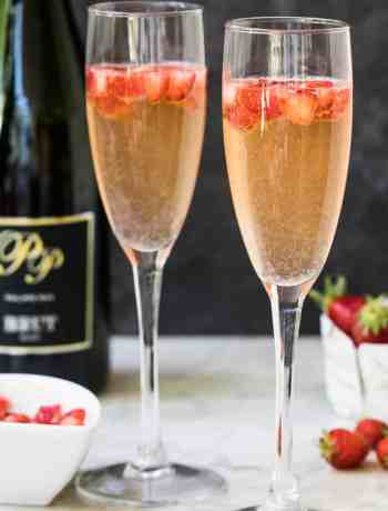 two champagne glasses with strawberry mimosa, with strawberries and champagne bottle in background