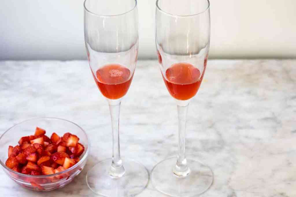 two glasses of champagne filled with a small amount of strawberry syrup and bowl of strawberries