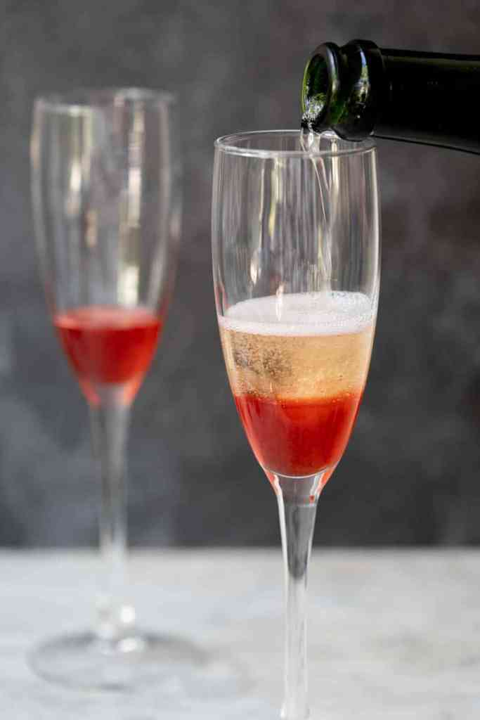 pouring champagne over strawberry syrup