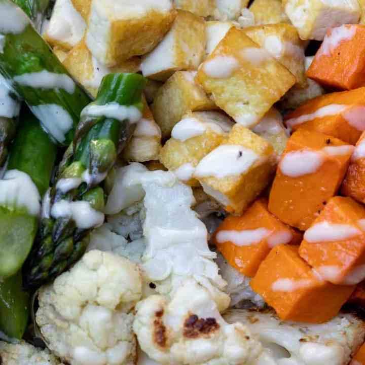 close up of vegan buddha bowl showing asparagus, tofu, sweet potatoes, cauliflower and quinoa