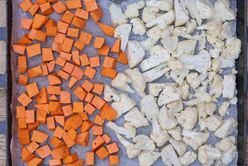 chopped sweet potatoes and cauliflower florets tossed in olive oil on parchment-lined sheet pan