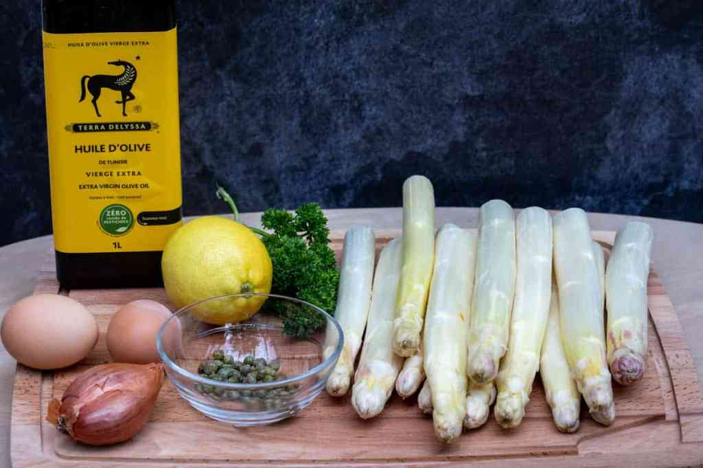 cutting board with shallot, capers, lemon, parsley, white asparagus, eggs, olive oil in front of dark background
