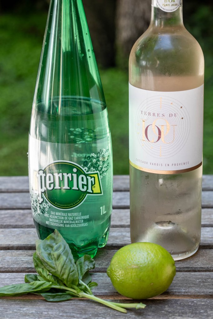 bottle of Perrier, bottle of rosé, lime, basil