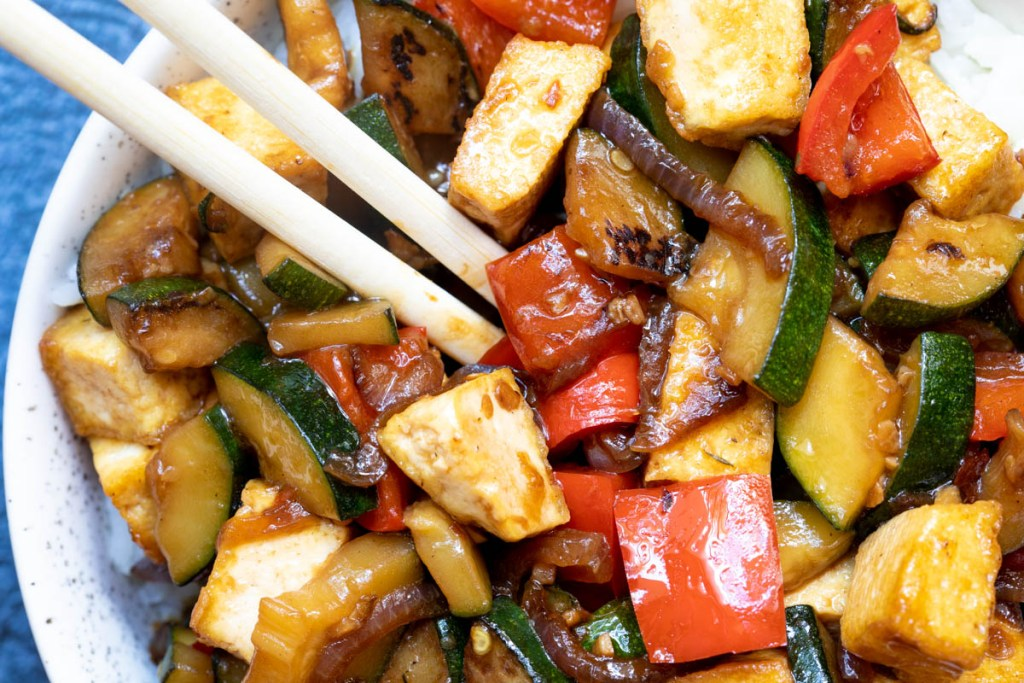 close up of zucchini stir-fry with tofu and red pepper in bowl with chopsticks