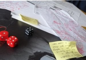 Crumpled up papers and post-its and dice