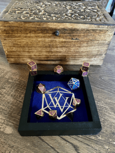 Blue dice tray with purple and gold metal dice and one large blue and silver metal dice