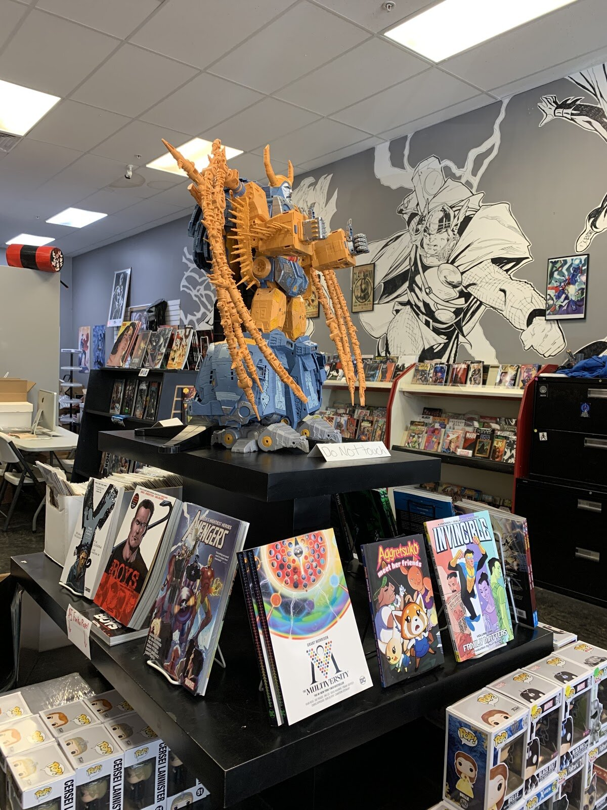 Large robotic figure stands over display of graphic novels