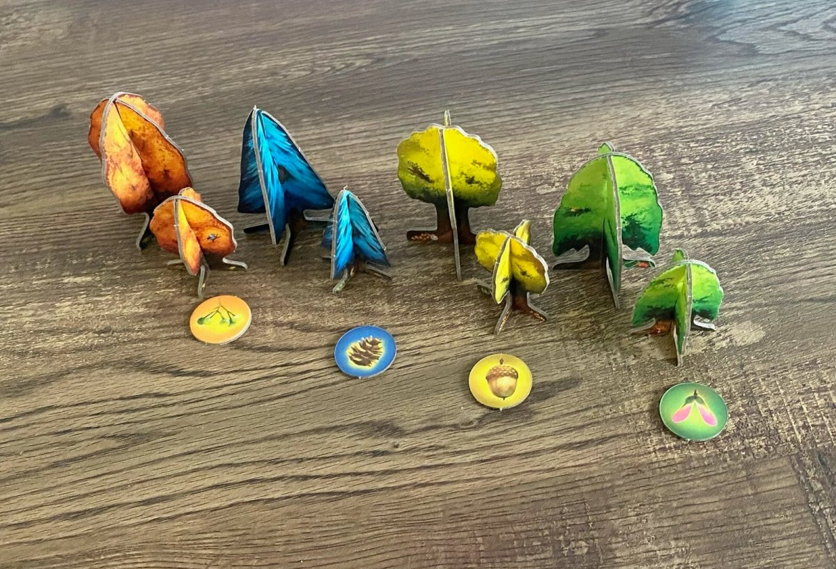 Game pieces of all four trees in different sizes, with seed token