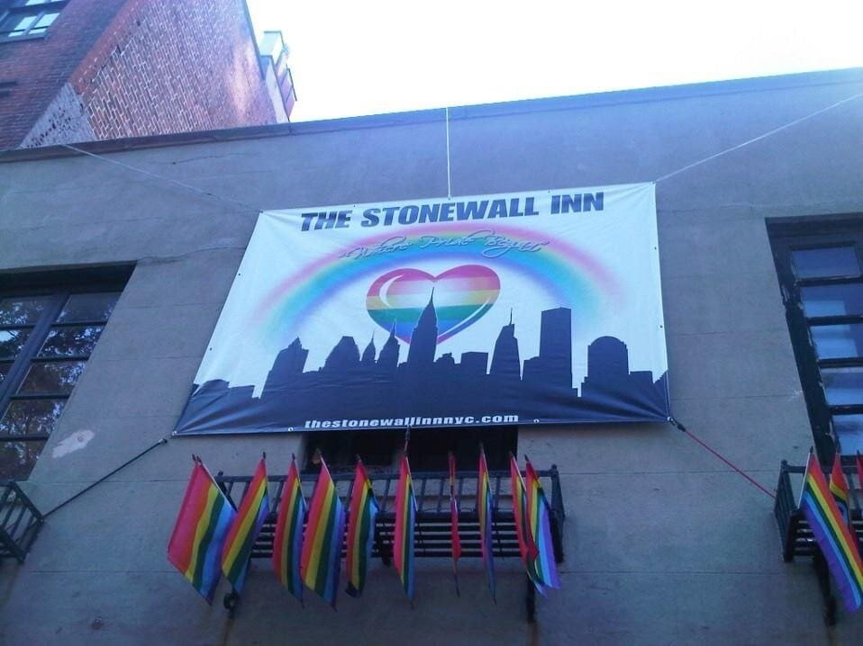 Banner Reading The Stonewall Inn hangs on a building with many pride flags