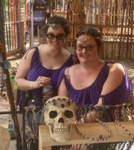 Two women in purple shifts sit behind a skull with a jeweled headpiece. The women are also wearing circlets.