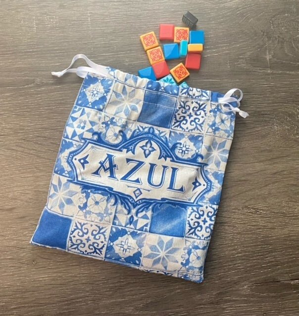 Pictured: A blue and white checkerboard Azul linen bag with multi-colored tile pieces spilling out of it.