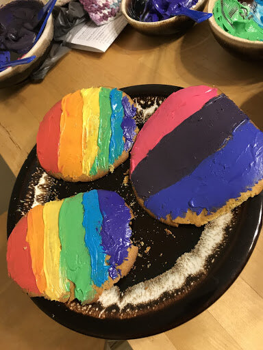 Three cookies; two frosted in red, orange, yellow, green, blue, and purple, and the last frosted in pink, purple, and blue, symbolizing the rainbow and bisexual flag, respectively.