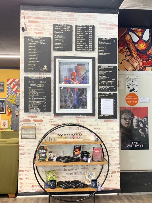 The menu at the BAMF Coffeehouse. A decorative display contains some flavorings and signage, above which hangs a framed Spider-Man poster surrounded by the menu of food and drink offered.