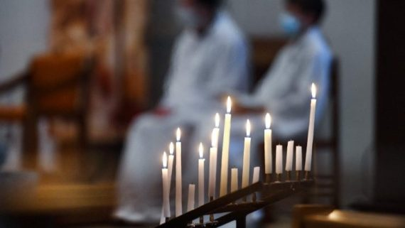 Candles are lit during mass in a Church in France