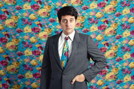 Comedian Ben Gleib in a suit and colorful tie against a bright floral background.