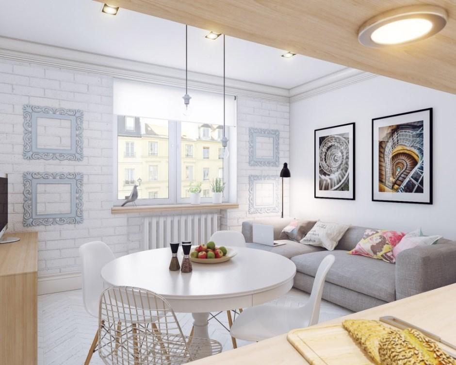 tavolo rotondo bianco con sedie in stile nordico bianche, su parete in mattoni bianchi e divano grigio
