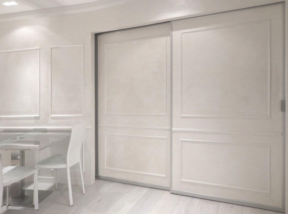 Porte scorrevoli bianche con cornici in gesso che dividono la cucina dalla camera