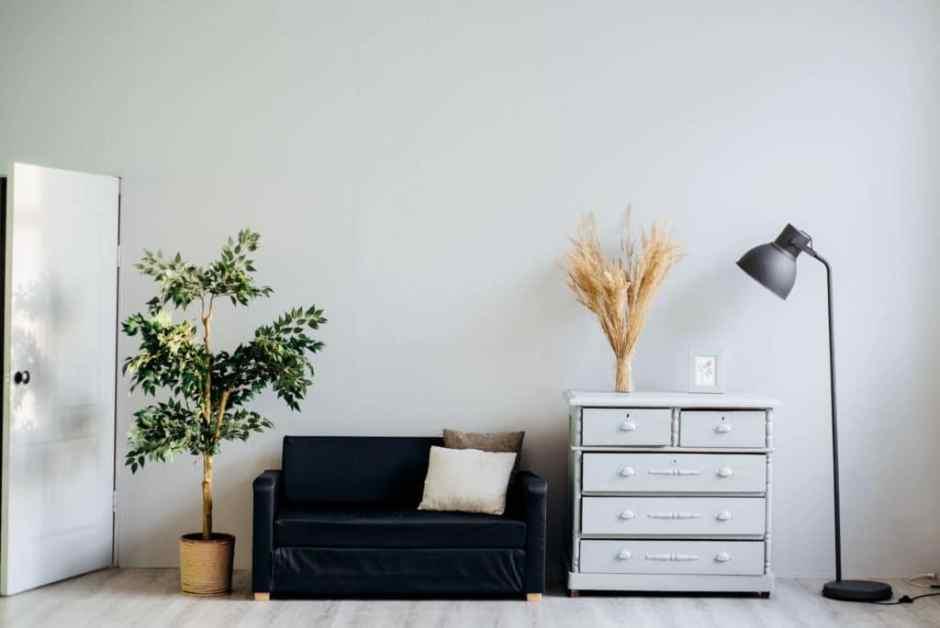 Vista frontale di un divano a due posti in velluto nero, una cassettiera vintage ed una lampada da terra in stile nordico.