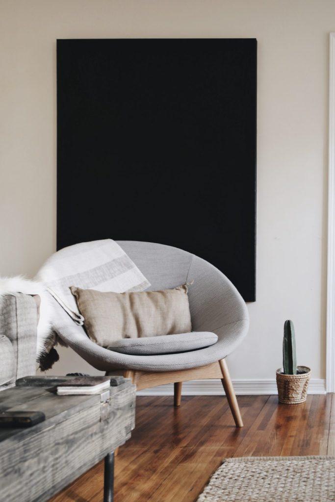 Dettaglio di una poltrona grigia moderna con cuscino e coperta, posizionata davanti ad una tela nera.