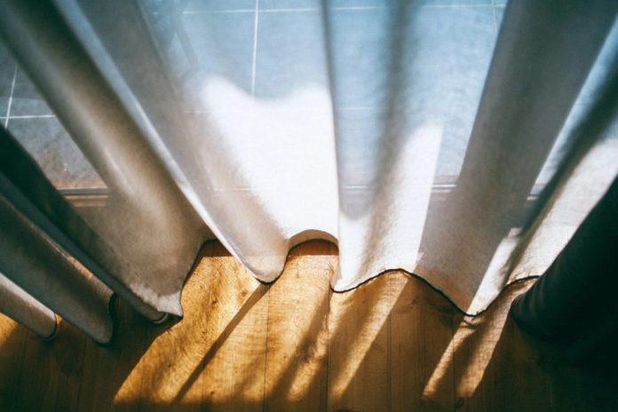 Vista dall'alto di una tenda chiara su un parquet scuro.