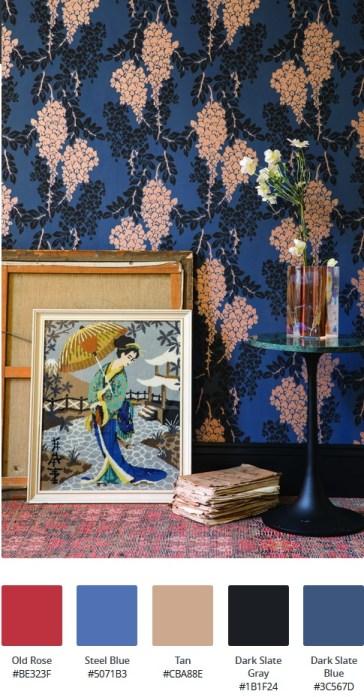 Cos'è lo stile d'arredo massimalista: interno con carta da parati floreale a fondo blu, quadri a tema Giappone, tavolo da caffè rotondo con piano in marmo verde, vaso trasparente con fiori bianchi e tappeto rosso