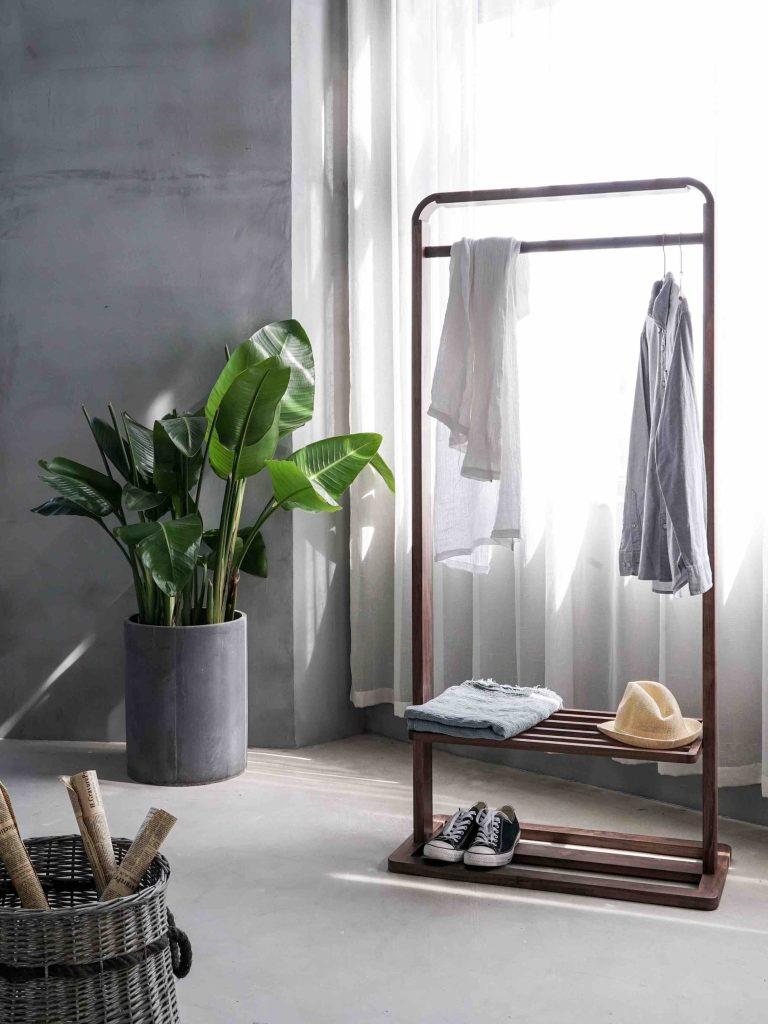 comprare online per arredare appendiabiti in legno con camicia appesa e scarpe da tennis, con pianta tropicale a fianco.