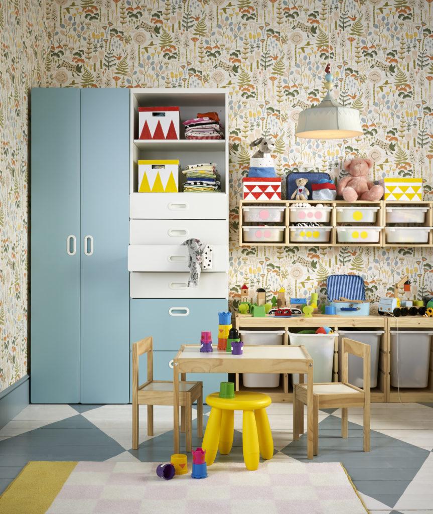 Tavolo e sedie piccole per bimbi, con armadio azzurro sul fondo e contenitori per giochi