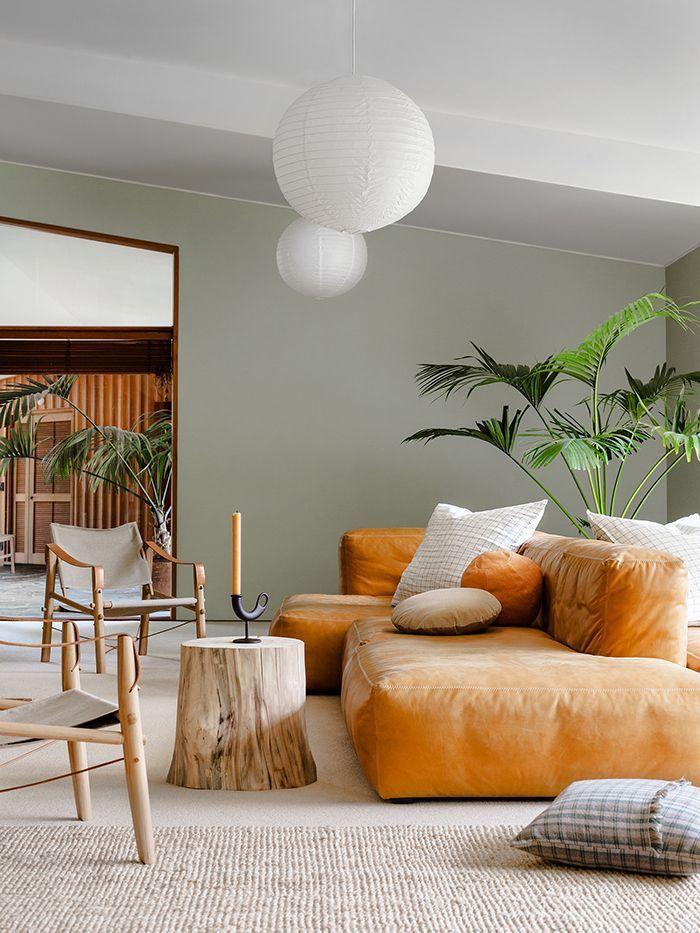 soggiorno con pareti verde chiaro e divano arancione