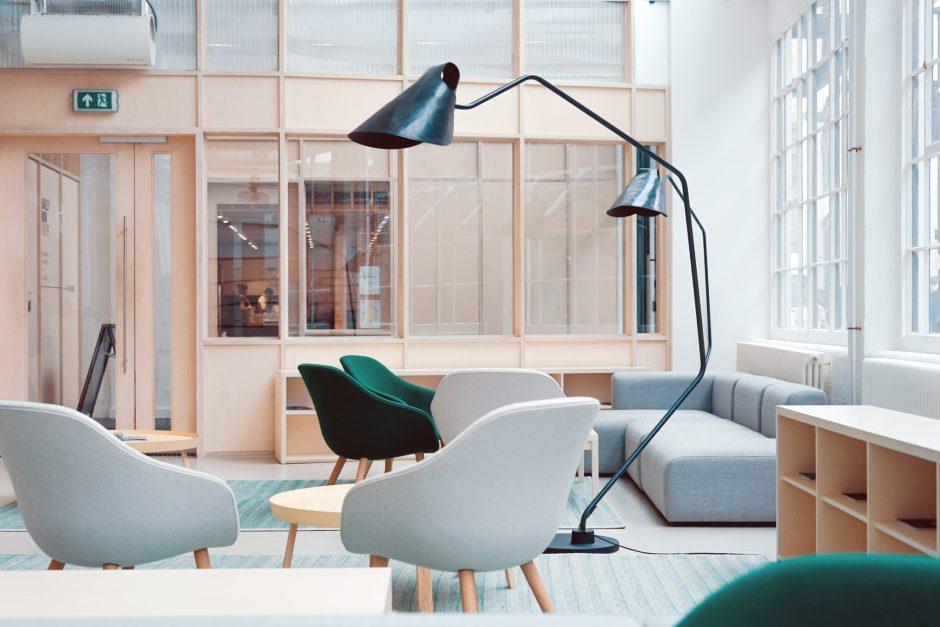 soggiorno in stile scandinavo con poltrone in tessuto grigio e verdi e grande lampada da terra nera