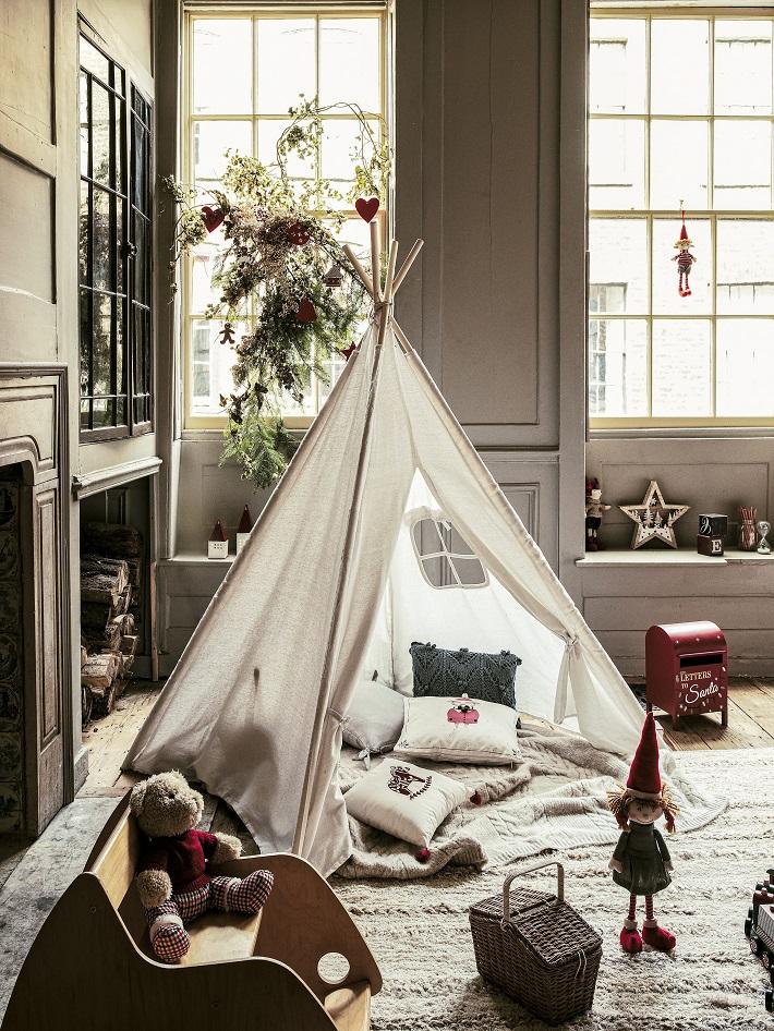 Cameretta in stile classico con tepee, tappeto a pelo corto e pupazzi natalizi