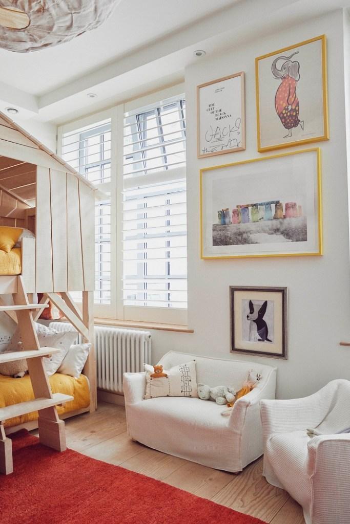 cameretta con letto a castello, quadri astratti a parete, divani bianchi e finestre con vasistas superiore