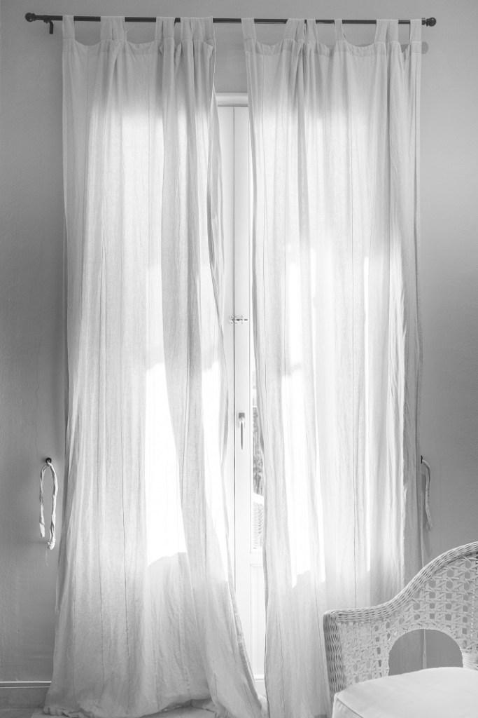 come scegliere le tende: tende bianche con patte a vista e bastone nero