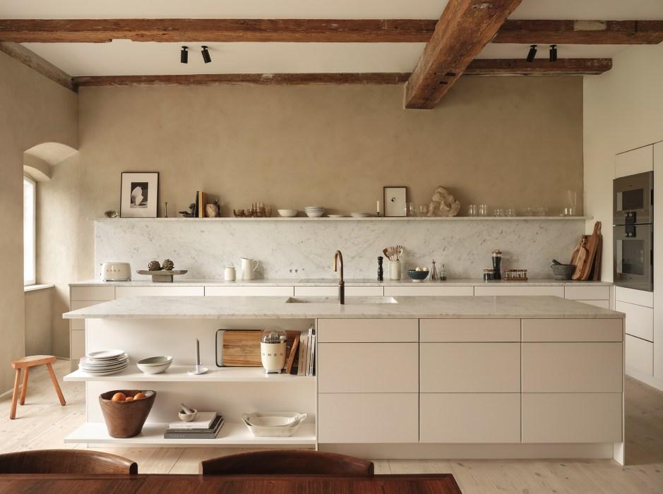 Cucina con basi ed isola bianche, senza pensili. Muro a calce beige e soffitto a travi in legno.