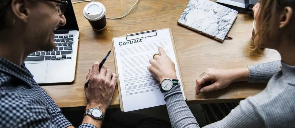 """Two people sitting, reading a contract; on the table there is a document titled """"Contract"""", a laptop, coffee, and many sockets"""