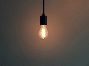 A light bulb and a dark background, the light is on.