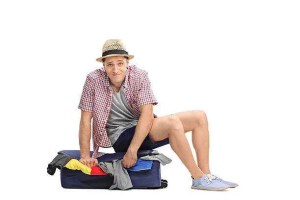 A young man sitting on a suitcase full of clothes, trying to close it