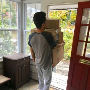 A man carrying boxes through the front door